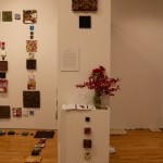 Photo of left wall of right wall of installation. The side of the wall has three bricks at the top. In the center, is the artist's statement. A pedestal is placed in front of the wall with more bricks on its side. On top of the pedestal is a notebook with pens, postcards for the show, and a vase with red and pink flowers. To the right of the wall with the title of the show, bricks of varying size and material are laid out on the ground. The left side of the wall shows the main installation of bricks on the wall and laid out carefully on the ground.