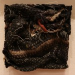 Photo of untitled. This is a square brick made out of a fabric, woven place-mat and hung on a gallery wall. The fabric is black, light gray, blue, and some red. It is woven together with white string, but some of the stitching has come undone.