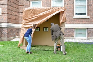 Installation piece, cardboard, wood, tarps, photos, frames, and found objects.