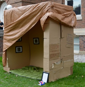 Cardboard, wood, tarps, photos, frames, and found objects.