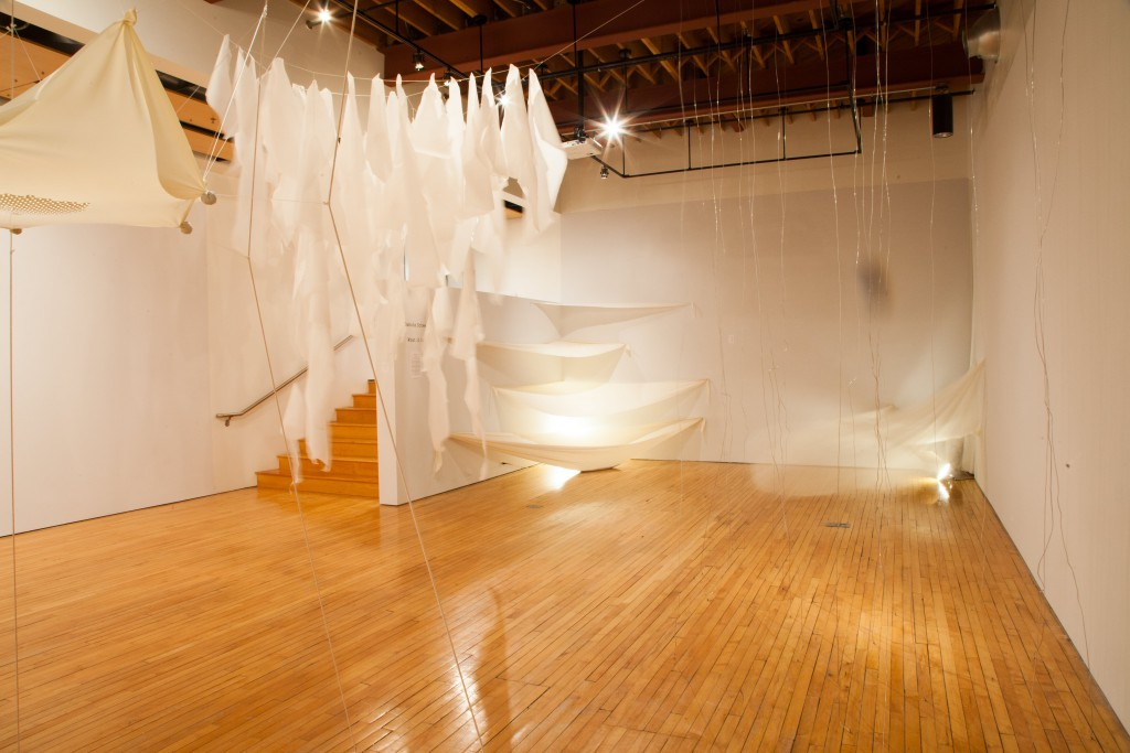 Layers of torn paper are closest in view, behind them are fan-shaped pieces of cotton stretched in the corner, full of dried black beans. A cluster of silver wire hangs vertically from ceiling to floor, bent and twisted. In the other corner, behind the wire, sheer fabric is blown in the air by a fan