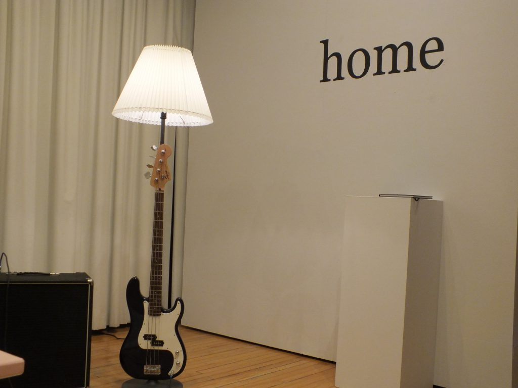"The bass lamp is lit by its bulb standing upright next to the title for the show and pedestal for the guestbook. ""home"""