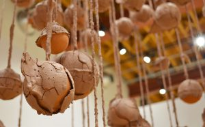 Close up of a group of terracotta spheres hang from twine, covered in dry, unfired slip. The slip is shrinking and cracking off of the spheres, exposing the bright orange fired terracotta underneath.