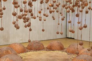 Terracotta spheres hang from twine, covered in wet slip. Base platform is a decagon made of plywood and raised by wooden boards. Eight large half spheres made of terracotta sit on the plywood. They have the unfired slip dripped and poured on them. There is an opening in which the viewer can stand on the base, surrounded by the spheres.