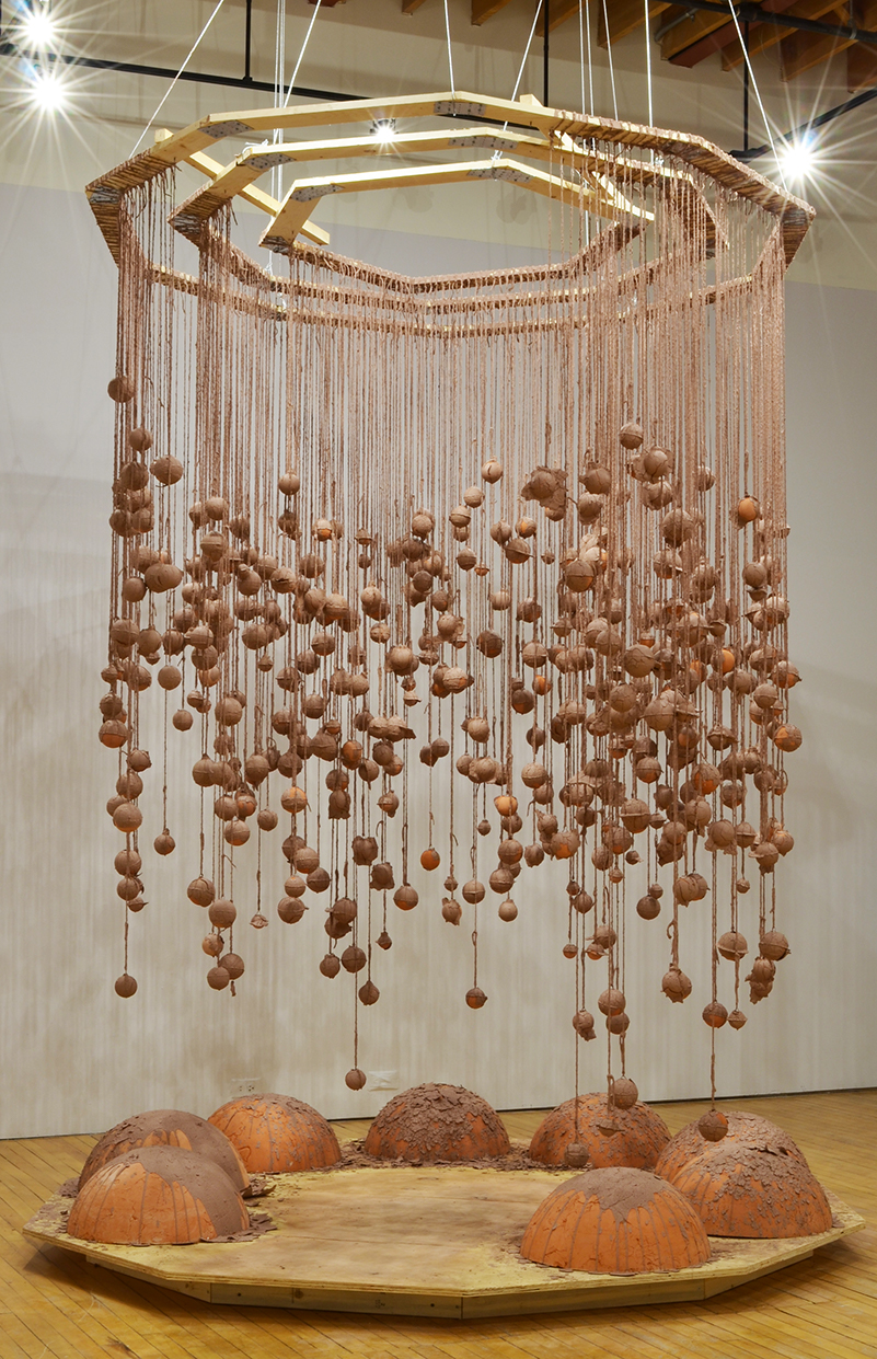 Installation photo, the whole piece is shown. Hundreds of terracotta spheres hang from twine, covered in wet slip. The twine is attached to three intrinsic geometric wooden frames. Dramatic shadows are cast against the gallery walls. Base platform is a decagon made of plywood and raised by wooden boards. Eight large half spheres made of terracotta sit on the plywood. They have the unfired slip dripped and poured on them.