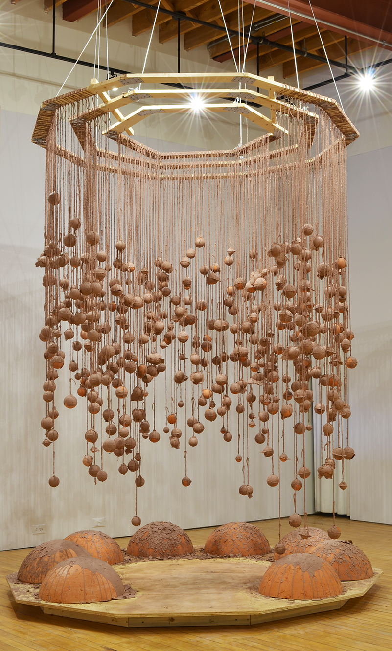 Installation photo, the whole piece is shown. Hundreds of terracotta spheres hang from twine, covered in wet slip. The twine is attached to three intrinsic geometric wooden frames. Dramatic shadows are cast against the gallery walls. Base platform is a decagon made of plywood and raised by wooden boards. Eight large half spheres made of terracotta sit on the plywood. They have the unfired slip dripped and poured on them. There is an opening in which the viewer can stand on the base, surrounded by the spheres.