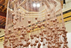 Installation photo, cropped to show the shadows on the wall. Hundreds of terracotta spheres hang from twine, covered in wet slip. The twine is tied to three intrinsic geometric wooden frames. Interior
