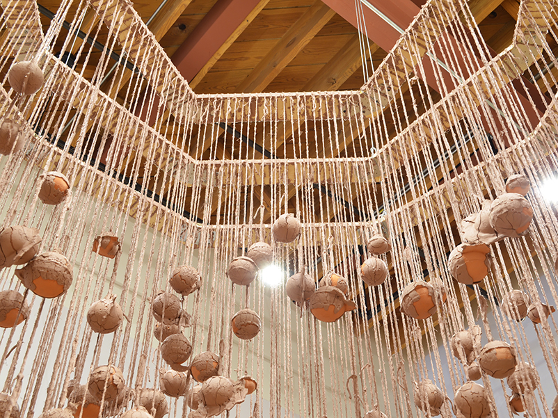Installation photo, cropped to show the shadows on the wall. Hundreds of terracotta spheres hang from twine, covered in wet slip. The twine is tied to three intrinsic geometric wooden frames. Interior of frames.