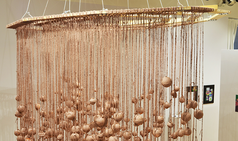 Installation photo, cropped to show the shadows on the wall. Hundreds of terracotta spheres hang from twine, covered in wet slip. The twine is tied to three intrinsic geometric wooden frames.