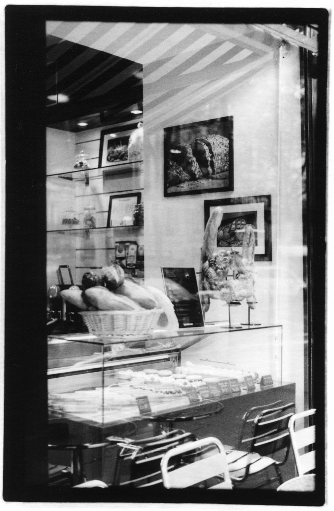 Black and white photo of a bread shop window. Inside is a basket of bread and photos of bread. In the reflection is a table and chair outside of the store.