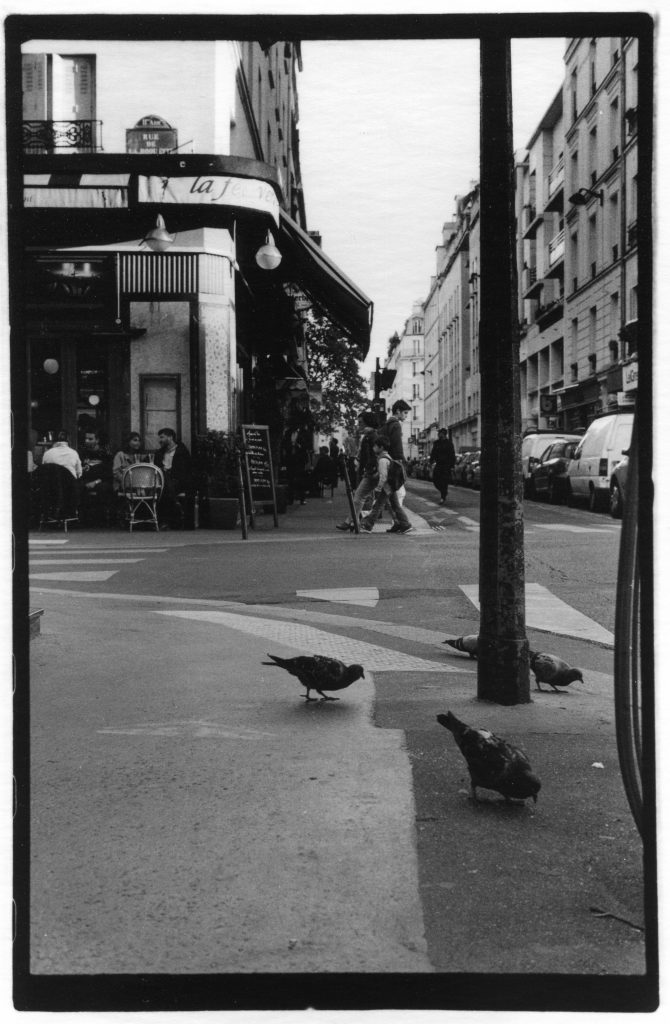 Black and white photo of pigeons on a street corner, they take up the bottom right foreground of the photo, while a case if in the background. There are people crossing the street and sitting at the cafe in the background as well.