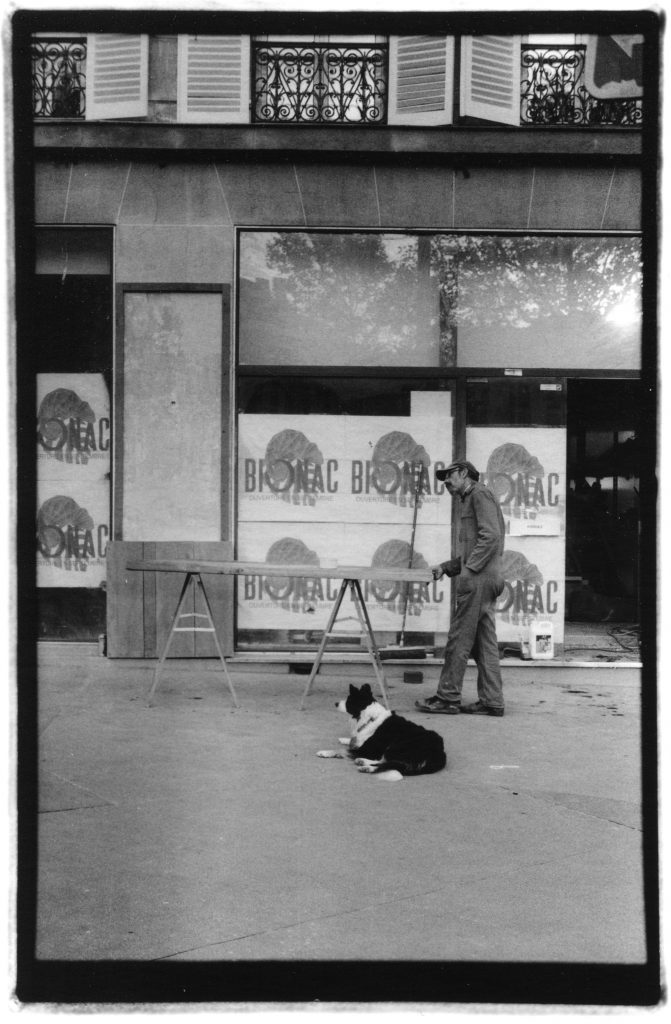 Black and white photo of a male construction worker holding onto the edge of a propped up plank. He has a border collie dog laying below him. They are both looking in the same direction.