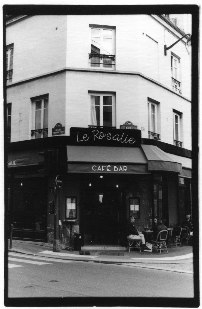 "Black and white photo of a cafe on the corner of a street. There is the words ""Le Rosalie"" written in a pretty cursive font, and ""Cafe Bar,"" written in a more modern eclectic font."