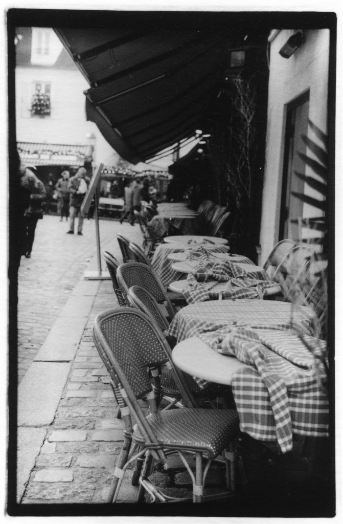Black and white photo of chairs and tables outside of a French cafe. There is a disheveled checkered tablecloth on the table in the foreground.