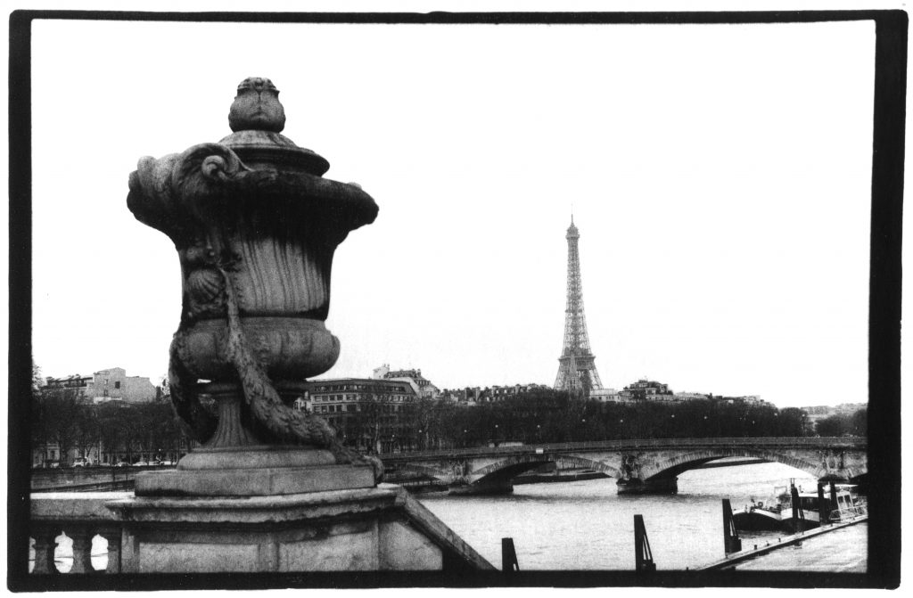 Black and white photo of the Eiffel Tower. In the foreground is a decorative statue.