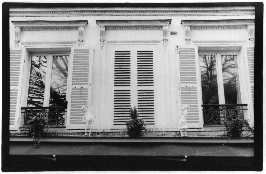 Black and white photo of a window with shutters. There is a plant in the middle of the photo and tiny figurines of a boy and a girl on either side.