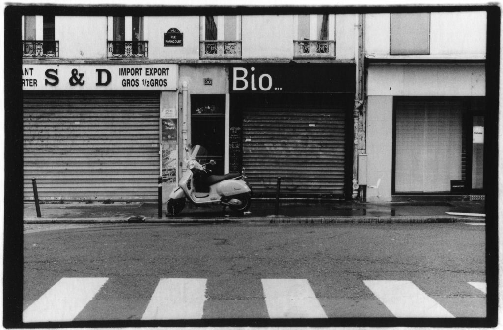 "Black and white photo of a scooter in front of a row of buildings. They have the words ""Bio"" and the letters ""S"" and ""D"" written on them."