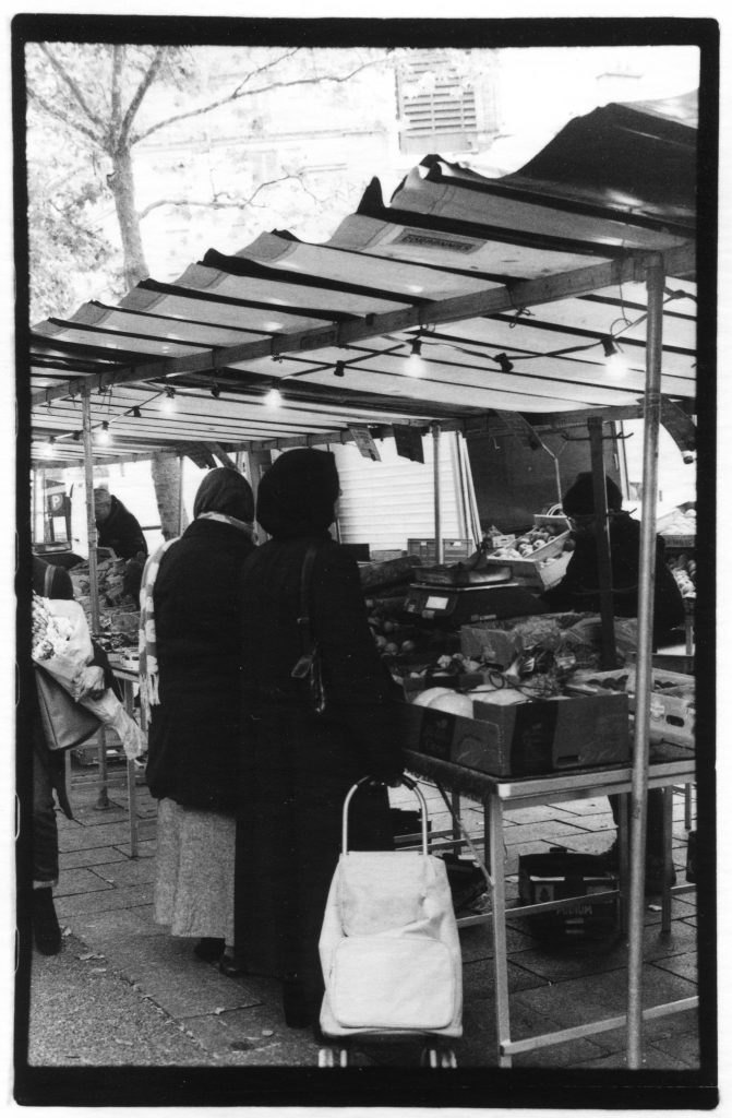 Black and white photo of the back of two women in hijabs. They are shopping at an outdoor farmer's market.