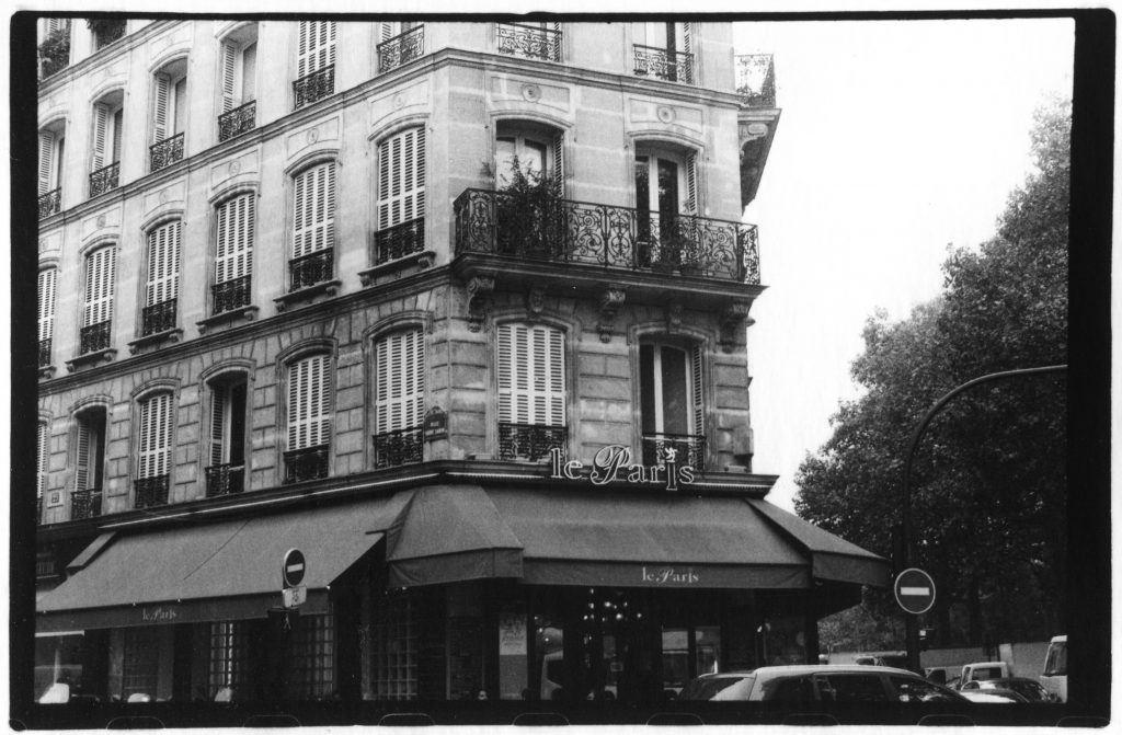 "Black and white photo of a French cafe on a corner. It reads the words ""Le Paris."" The building appears to be very old."