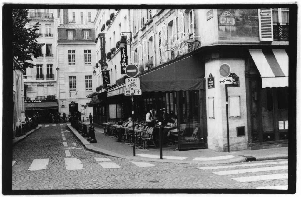 Black and white photo of a street corner. There is a french cafe on the corner with a man sitting outside. In the background are buildings. There are many street signs spread long this street.