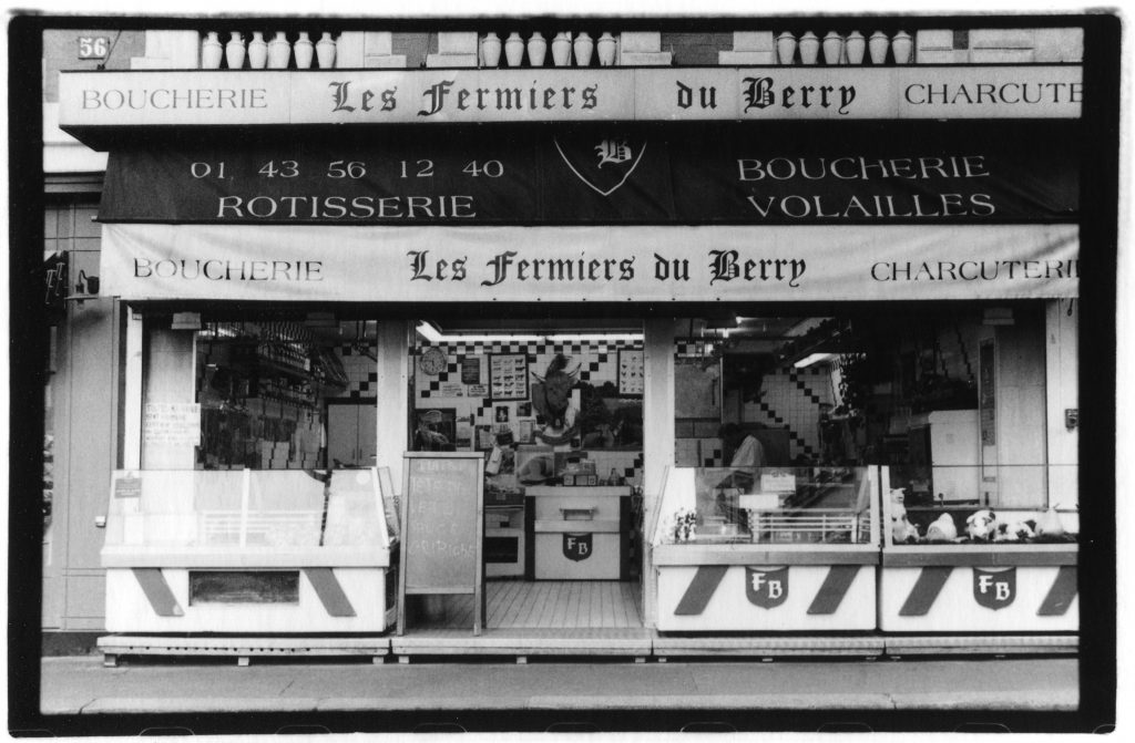 Black and white photo of a store front that is selling cheese. There are a variety of fonts with French words written all over. There is the head of a bison mounted in the middle of the inside of the store.