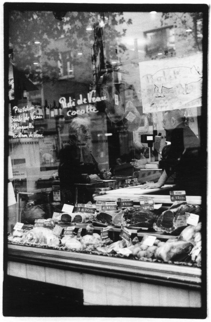 Black and white photo looking into the window of a meat shop. There is a man purchasing meat from someone behind a counter. There are meats in the foreground of the window and reflections of text in the glass window.