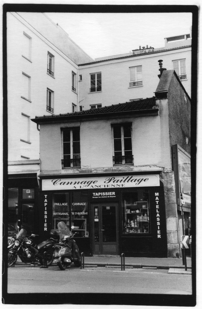 Black and white photo of a buildind on a street corner. There is French writing o n the building and motorcycles parked outside.