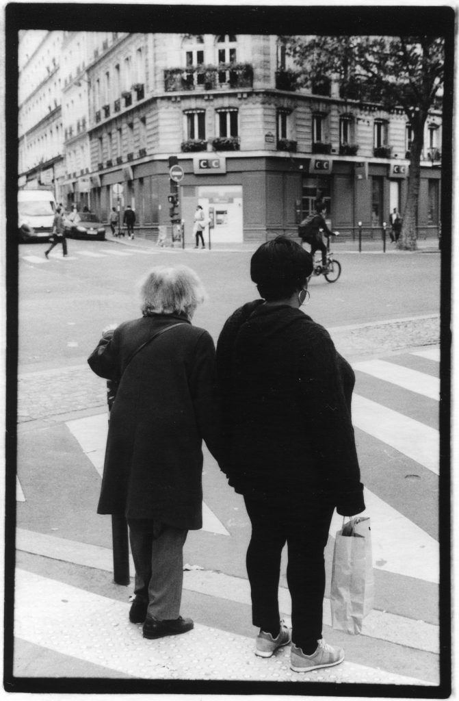 Black and white photo taken from the back of two women holding hands. They are standing on a street corner with bicyclists and cars in front of them.