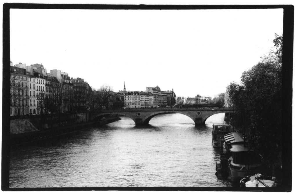 Black and white photo of the Seine in Paris. There is a bridge in the background, and buildings behind the bridge.