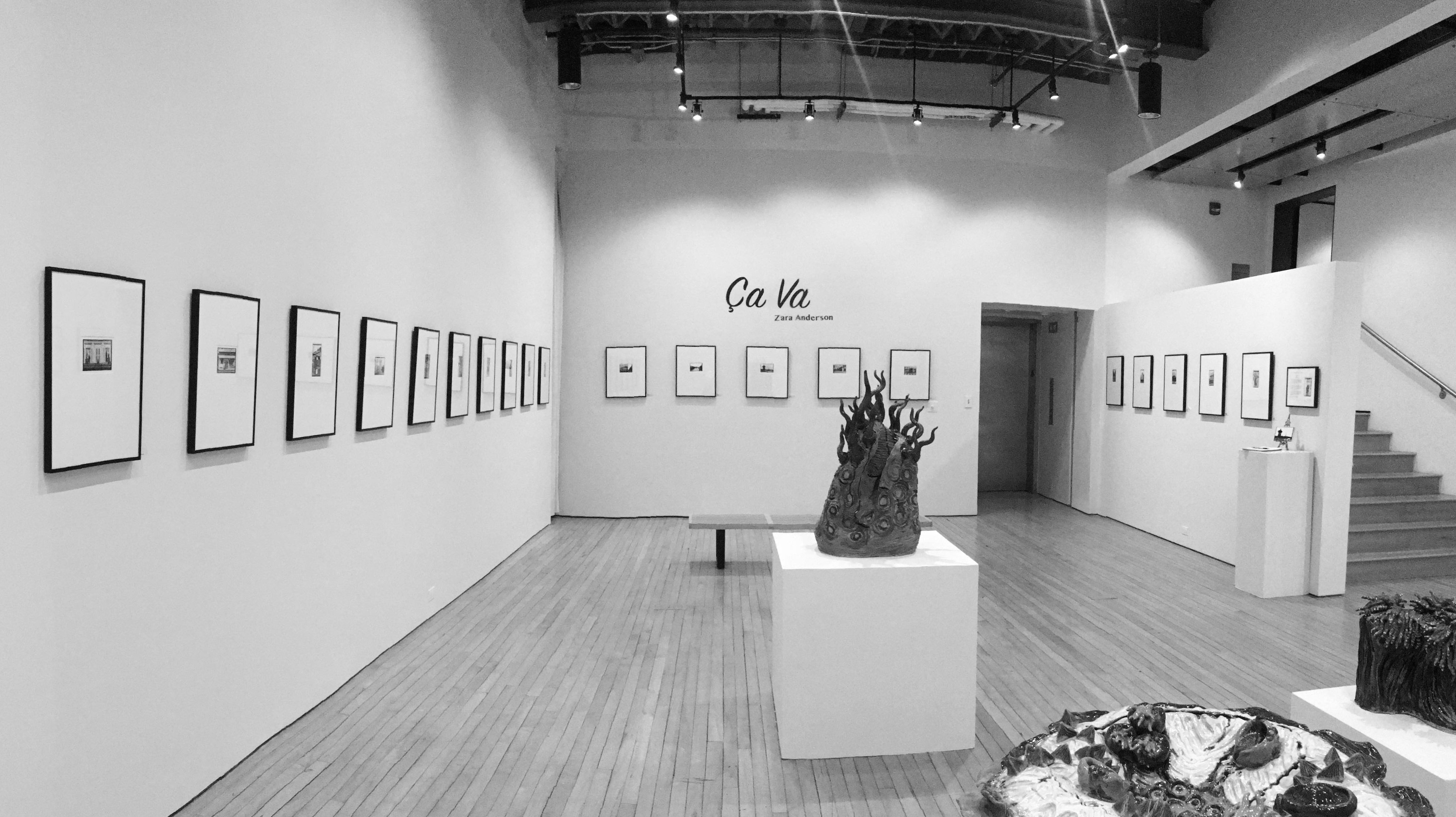 "Black and white photo of gallery space. Photos that are matted and framed line the wall, and the phrase ""Ca Va"" with the name ""Zara Anderson"" is on the middle of the wall."